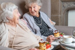 Two ladies enjoying cake and tea in a care home