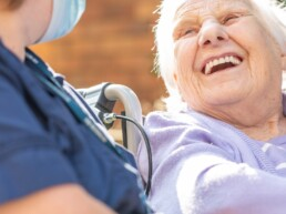 Autograph Care Home resident and carer enjoying a laugh in the garden