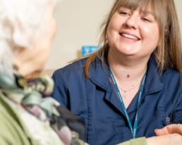 A carer working in a care home smiling talking to a resident